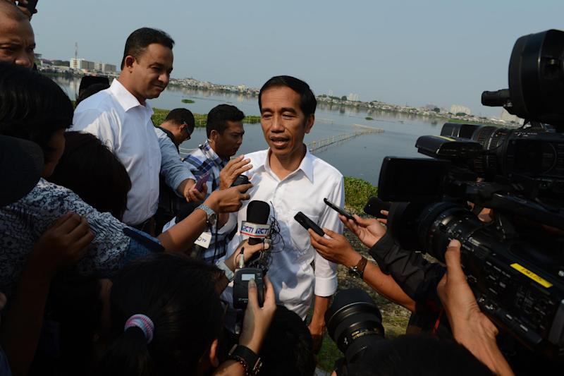 Indonesian presidential candidate Joko Widodo (centre) intervied by journalists at an urban development project in Jakarta, on July 22, 2014