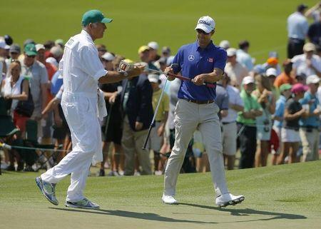 Australia's Adam Scott takes his putter from caddie Steve Williams on the second hole during the third round of the Masters golf tournament at the Augusta National Golf Club in Augusta, Georgia April 12, 2014. REUTERS/Brian Snyder/Files