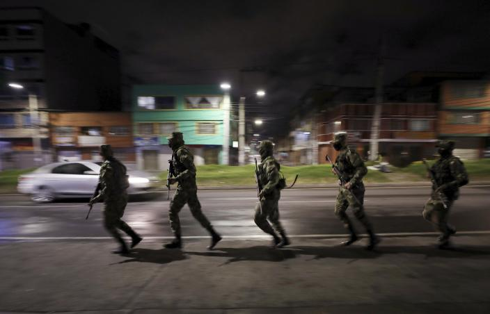 Soldiers run to a military truck to change checkpoint during an official continuous multi-day curfew in an effort to contain the spread of new coronavirus infections, in Bogota, Colombia, Friday, Jan. 22, 2021. Colombia's capital city is reimposing lockdown measures as COVID-19 infections rise around the country. (AP Photo/Fernando Vergara)