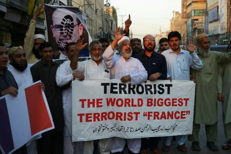 Traders shout slogans as they hold a banner and a poster of French Prime Minister Jean Castex, with a footprint over his face, during a protest following French President Emmanuel Macron criticised Islamists, in Peshawar, Pakistan
