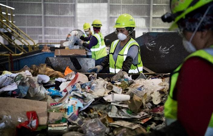 """Some workers must go through the recyclables by hand to remove items seen as """"contaminants"""" (AFP Photo/SAUL LOEB)"""