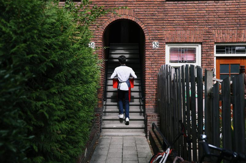Sam Spijkerman walks up the stairs delivering groceries to a customer in Amsterdam