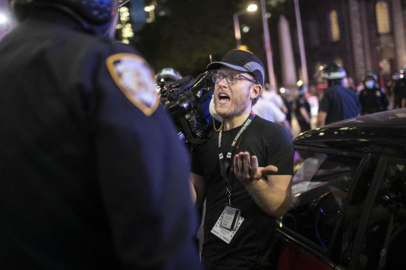 """Associated Press videojournalist Robert Bumsted reminds a police officer that the press are considered """"essential workers"""" and are allowed to be on the streets despite a curfew, Tuesday, June 2, 2020, in New York. New York City police officers surrounded, shoved and yelled expletives at two Associated Press journalists covering protests in the latest aggression against members of the media during a week of unrest around the country. Portions of the incident were captured on video by Bumsted, who was working with photographer Wong Maye-E to document the protests in lower Manhattan over the killing of George Floyd in Minneapolis.(AP Photo/Wong Maye-E)"""