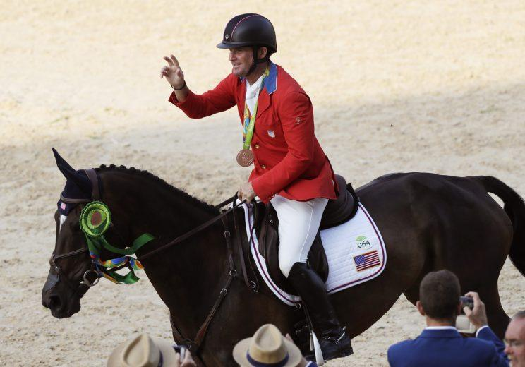 Phillip Dutton rides around the arena wearing his bronze medal (AP)