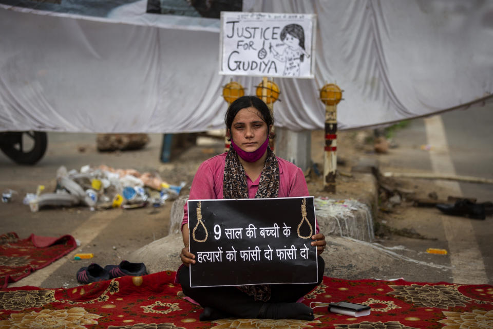 """Tina Verma, 27, a social activist, holds a placard which reads, """"Hang the killers of 9-year old child"""" at a demonstration site outside a crematorium where a 9-year-old girl from the lowest rung of India's caste system was, according to her parents and protesters, raped and killed earlier this week, in New Delhi, India, Thursday, Aug. 5, 2021. (AP Photo/Altaf Qadri)"""