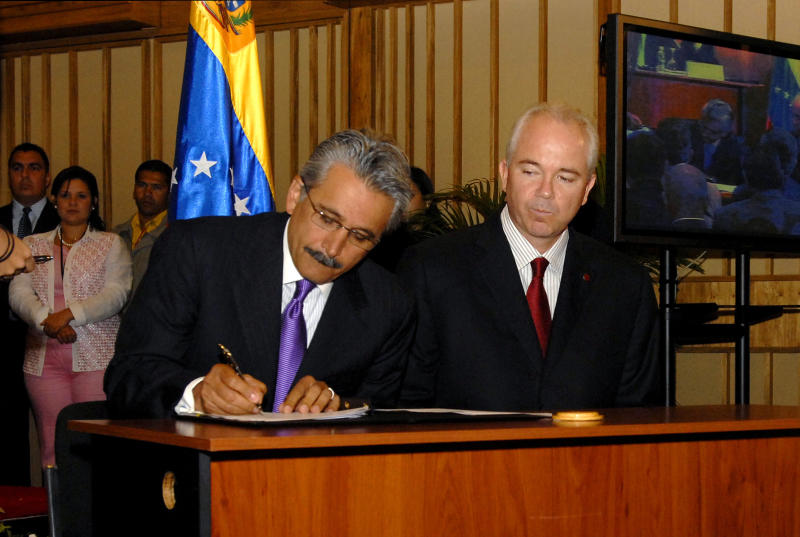FILE - In this June 26, 2007 file photo, then Chevron's top executive for Latin America Ali Moshiri signs a deal with Venezuela's state oil company Petroleos de Venezuela SA (PDVSA), as Venezuela's Energy Minister Rafael Ramirez watches, at PDVSA headquarters in Caracas, Venezuela. In 2007, as rivals Exxon and Conoco fled the country and sued amid a nationalization drive, Chevron rode alone in taking up Hugo Chavez's offer to form a joint venture with PDVSA on what were widely seen as unfavorable terms. (AP Photo/Gregorio Marrero, File)