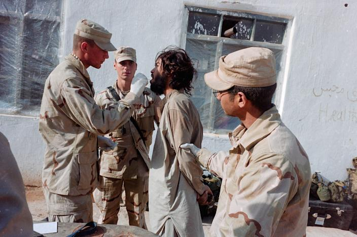 A soldier takes a mouth swab from a prisoner.
