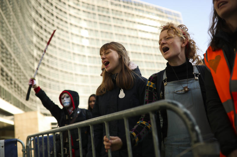 Youngsters shout slogans during a small protest by Extinction Rebellion climate change activists outside the European Commission headquarters in Brussels, Thursday, Oct. 31, 2019. (AP Photo/Francisco Seco)