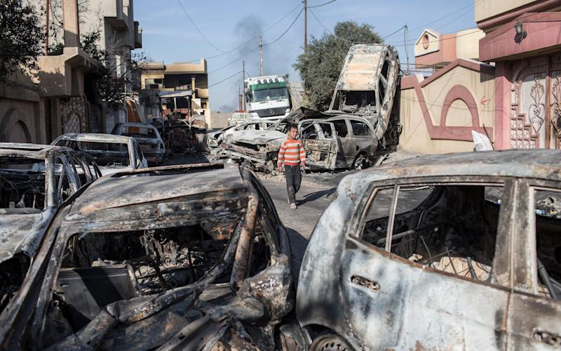 A boy walks past cars that were burned to create a smokescreen for ISIS fighters, in the neighbourhood of Sammod, on the southern edge of western Mosul - Credit:  Sam Tarling