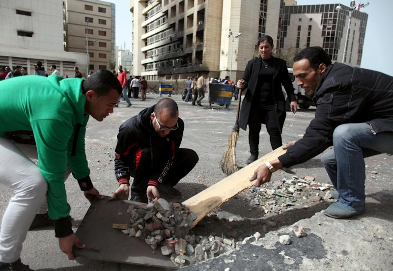 Egyptians clean up the streets from stones as the army takes over control of the state security building after several days of clashes between protesters and riot police in Port Said, Egypt, Friday, March 8, 2013. With the country in chaos from weeks of protests against the Islamist president, the police have now joined the fray, launching their own protests. Some security forces in Port Said have refused to leave their barracks to move against protesters in the street amid clashes raging for days. Others have refused orders to deploy to Port Said from elsewhere to help in the fight. (AP Photo/Khalil Hamra)