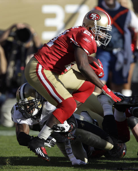 """FILE - In this Jan. 14, 2012 file photo, San Francisco 49ers running back Frank Gore (21) is tackled by New Orleans Saints strong safety Roman Harper (41) during the second quarter of an NFL divisional playoff football game, in San Francisco. A newly released recording purports to capture former Saints defensive coordinator Gregg Williams telling players to """"put a lick"""" on San Francisco's Kyle Williams to see if the receiver has lingering effects from an earlier concussion. In the recording from a meeting before the Saints played the 49ers in a playoff game in January, Williams urges players to beat running back Frank Gore's head, """"lay out"""" quarterback Alex Smith and go after receiver Michael Crabtree's knee. (AP Photo/Paul Sakuma, File)"""