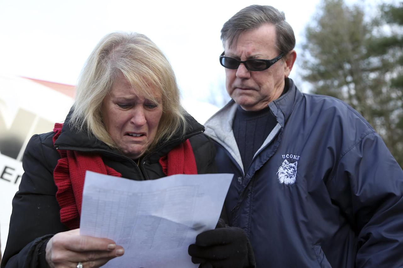 "Kathy Murdy, left, and her husband Rich Murdy react as they look at the list of victims of the Sandy Hook elementary school shooting, Saturday, Dec. 15, 2012 in Sandy Hook village of Newtown, Conn. The victims of the shooting were shot multiple times by semiautomatic rifle, according to Connecticut Chief Medical Examiner H. Wayne Carver II, M.D. Carver called the injuries ""devastating"" and the worst he and colleagues had ever seen. Police began releasing the identities of the dead. All of the 20 children killed were 6 or 7 years old. Carver, said he examined seven of the children killed, and two had been shot at close range. When asked how many bullets were fired, he said, ""I'm lucky if I can tell you how many I found."" (AP Photo/Mary Altaffer)"