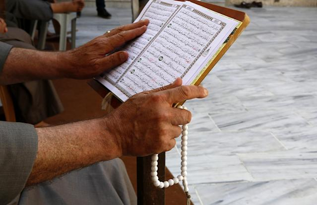 <p>A Palestinian man reads verses of the Quran, Islam's holy book, during the month of Ramadan at al-Omari mosque in Gaza City, May 29, 2017. (AP Photo/Hatem Moussa) </p>