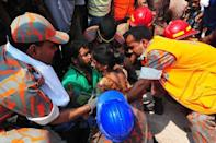 Bangladeshi firefighters rescue a garment worker who was found alive in the collapse of an eight-storey building in Savar, on the outskirts of Dhaka, on April 25, 2013. Dozens of workers were found alive Thursday as they huddled in the wreckage of a collapsed garment factory bloc in Bangladesh, a rare success for rescuers who have pulled out 256 bodies