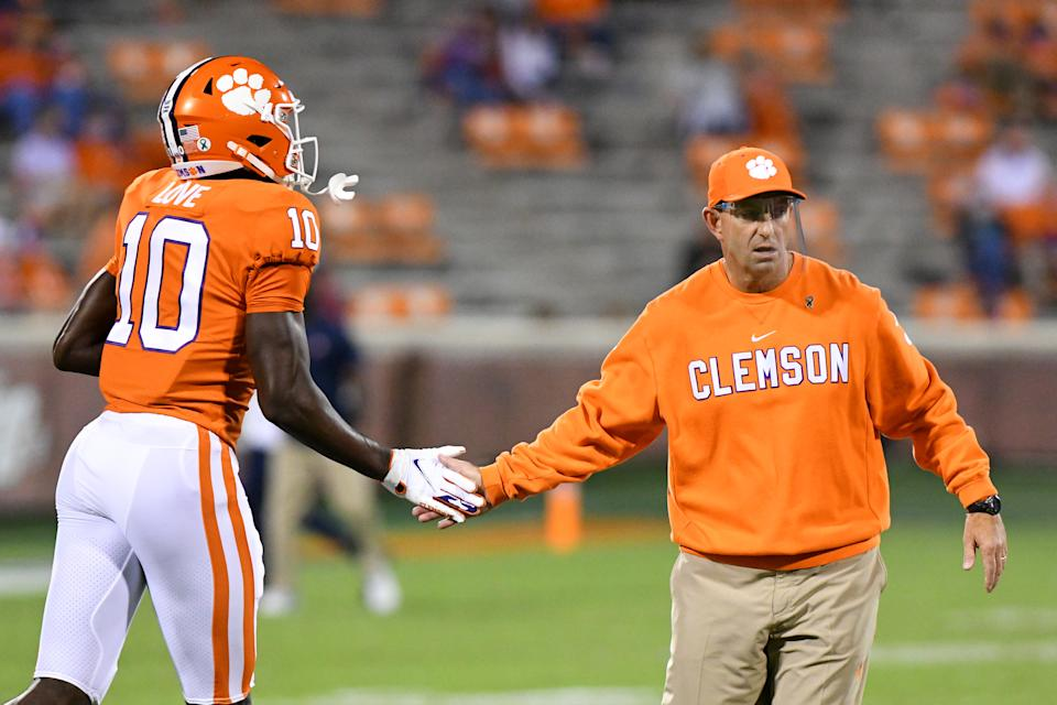 CLEMSON, SC - OCTOBER 03: Clemson Tigers head coach Dabo Swinney high fives Clemson Tigers wide receiver Joseph Ngata (10) prior to the game between the Clemson Tigers and the Virginia Cavaliers on October 03, 2020 at Memorial Stadium in Clemson, South Carolina. (Photo by Dannie Walls/Icon Sportswire via Getty Images)