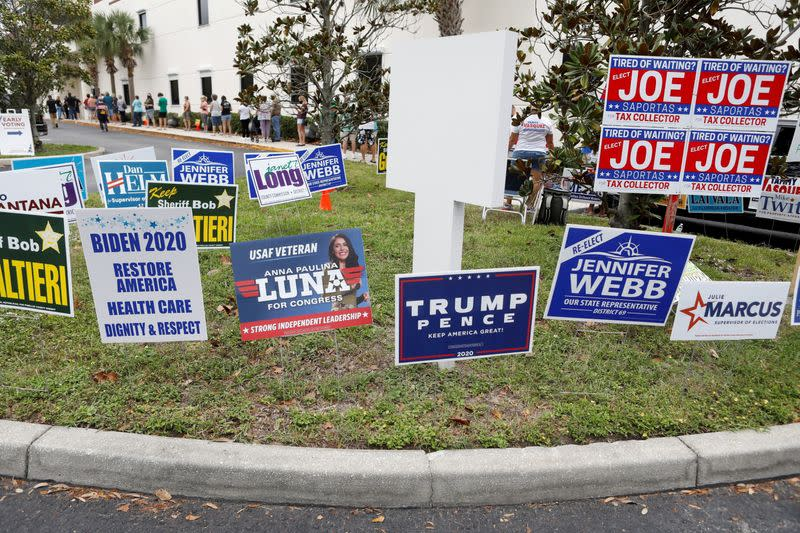 FILE PHOTO: Campaign signs are posted near the Supervisor of Elections Office polling station while people line up for early voting in Pinellas County ahead of the election in Largo