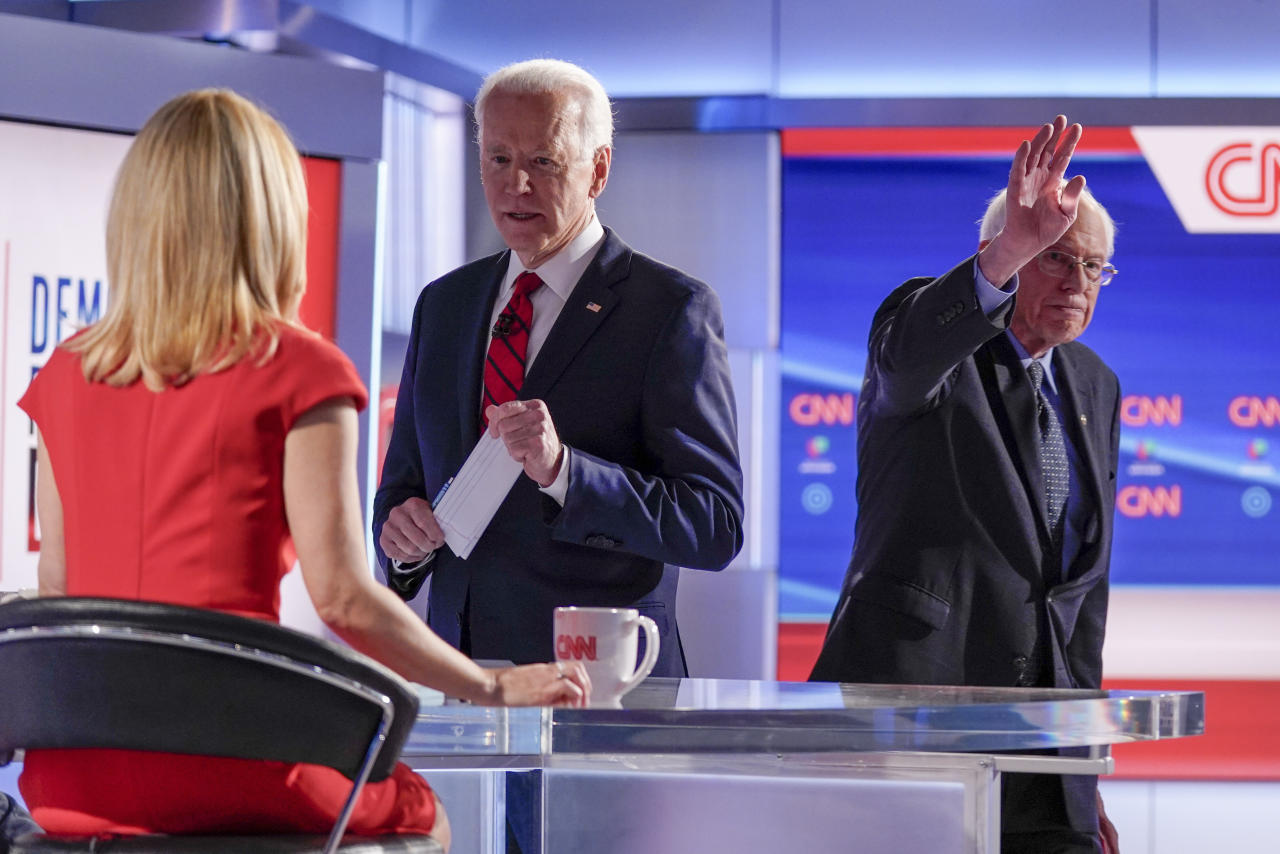 Former Vice President Joe Biden, center, stops to talk with CNN anchor Dana Bash, left, as Sen. Bernie Sanders, I-Vt., right, waves after they participated in a Democratic presidential primary debate at CNN Studios in Washington, Sunday, March 15, 2020. (AP Photo/Evan Vucci)