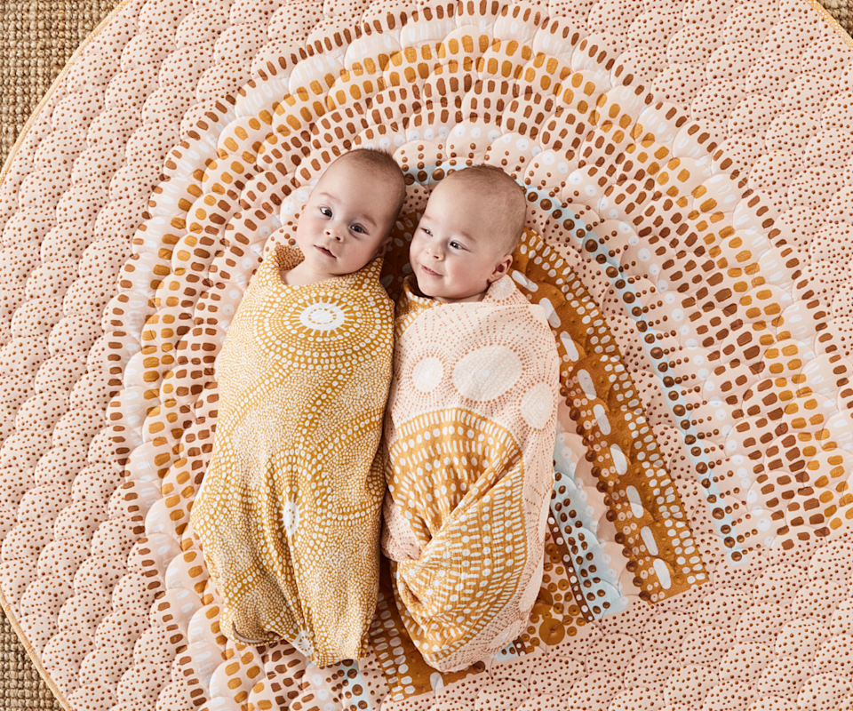Two swaddled babies lay on the ground next to each other ontop of an indigenous rainbow play mat.
