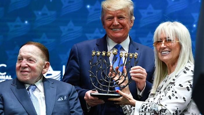 US President Donald Trump poses with Sheldon Adelson (L) and his wife Miriam Adelson ahead of his sddress ro the Israeli American Council National Summit 2019 at the Diplomat Beach Resort in Hollywood, Florida on December 7, 2019