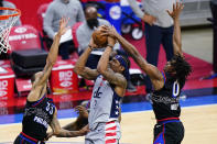 Washington Wizards' Bradley Beal, center, goes up for a shot against Philadelphia 76ers' George Hill, left, and Tyrese Maxey during the second half of Game 2 in a first-round NBA basketball playoff series, Wednesday, May 26, 2021, in Philadelphia. (AP Photo/Matt Slocum)