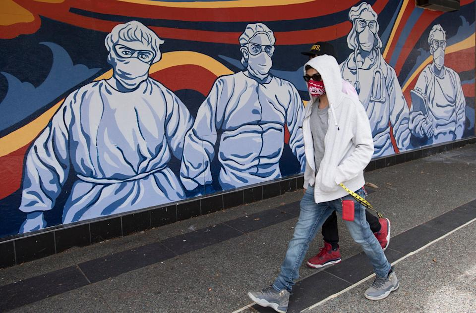 A man wearing a protective face mask walks past a mural of heath care workers painted on a boarded up restaurant in downtown Vancouver on April 27, 2020.  (Photo: Jonathan Hayward/THE CANADIAN PRESS)