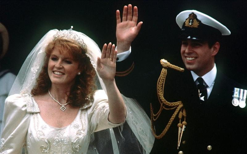 Prince Andrew and his bride Sarah Ferguson waving to crowds as they leave Westminster Abbey, London after their wedding ceremony