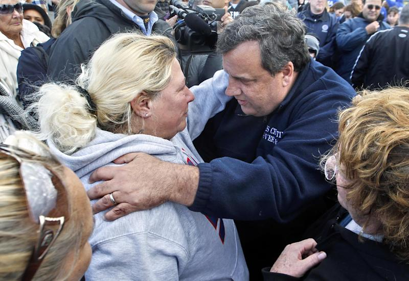 """FILE - In this Nov. 2, 2012 file photo, New Jersey Gov. Chris Christie, right, meets Bonnie Miller after touring devastation from Superstorm Sandy in Brick, N.J. Christie can't get enough of """"Saturday Night Live."""" One day after ducking questions about Twinkies-maker Hostess shutting down to avoid giving comedians fodder and saying he's on """"SNL"""" enough, Christie made a cameo appearance, Saturday, Nov. 17, 2012, on """"Weekend Update."""" The tough-talking governor poked fun at his notoriously short temper and the familiar blue fleece jacket that he has worn while touring the state following Superstorm Sandy. (AP Photo/Mel Evans, File)"""
