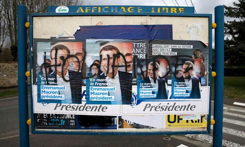Graffiti saying the name of the French president, François Hollande, scrawled over campaign posters for candidate Emmanuel Macron, in Villers-Cotterets