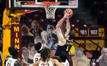 Michigan's Hunter Dickinson (1) shoots and scores as four against Minnesota players watch in the first half of an NCAA college basketball game, Saturday, Jan. 16, 2021, in Minneapolis. (AP Photo/Jim Mone)