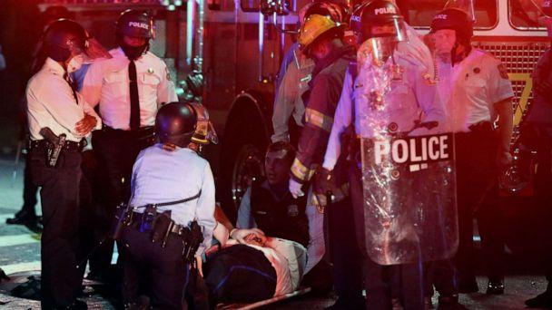 PHOTO: A police officer lies on the ground before being loaded into an ambulance on 52nd Street in West Philadelphia, Oct. 27, 2020. (Tim Tai/The Philadelphia Inquirer via AP)