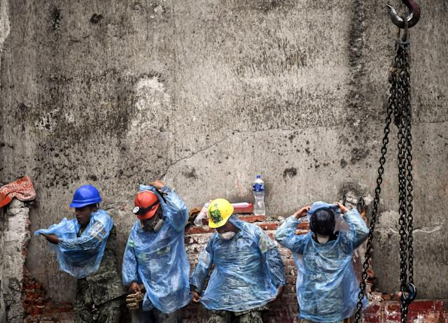 <p>Rescue workers put on rain gear during the search for survivors and bodies in Mexico City on September 21, 2017, two days after a strong quake hit central Mexico. (Photo: Ronaldo Schemidt/AFP/Getty Images) </p>