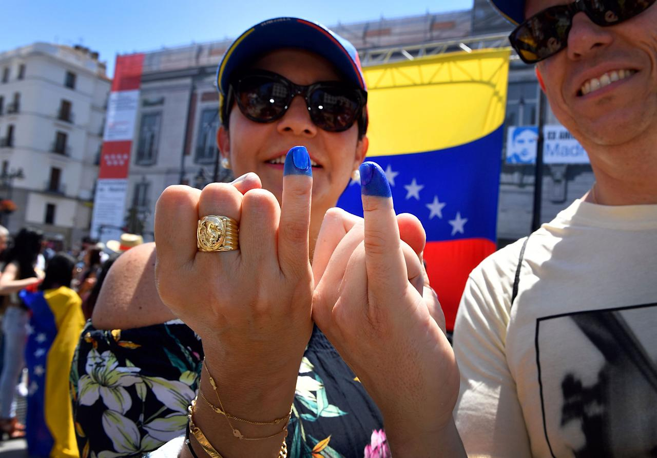 <p>Two Venezuelan residents in Madrid, show their little fingers stained with ink after voting during a symbolic plebiscite on president Maduro's project of a future constituent assembly, called by the Venezuelan opposition and held at the Puerta del Sol in Madrid on July 16, 2017. (Gerard Julien/AFP/Getty Images) </p>