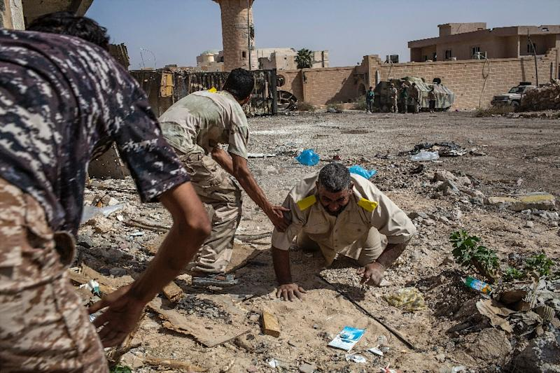 Fighters loyal to Libya's Government of National Accord help a wounded comrade after he was shot by an Islamic State (IS) group sniper on the western frontline in Sirte on October 2, 2016 (AFP Photo/Fabio Bucciarelli)