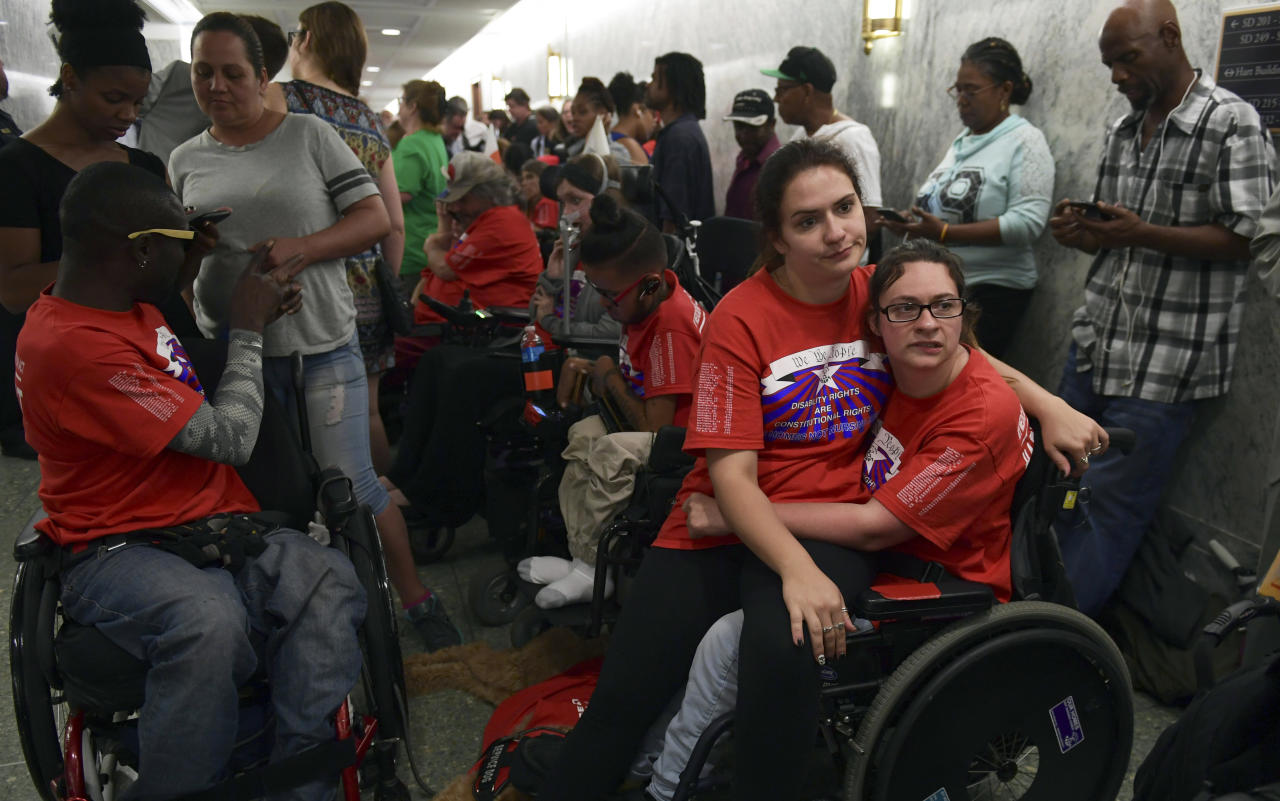 Shaylin Sluzalis, sits with her sister Brinnani Sluzalis, both of Williamsport, Pa., as they and others from a group called ADAPT, rally prior to a hearing by the Senate Finance Committee on the Graham-Cassidy health care repeal, on Capitol Hill in Washington, Monday, Sept. 25, 2017. Brittani receives Medicaid services. (AP Photo/Susan Walsh)