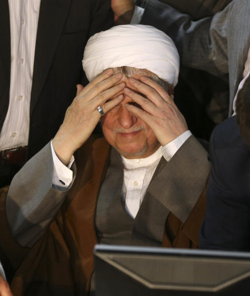 Former Iranian President Akbar Hashemi Rafsanjani puts his hands on his forehead as a gesture of respect to media, as he registers his candidacy for the upcoming presidential election, at the election headquarters of the interior ministry in Tehran, Iran, Saturday, May 11, 2013. Iranian election authorities say several new high-profile politicians including hardliners, reformists, and allies of outgoing President Mahmoud Ahmadinejad have registered for the June 14 presidential elections. The campaign is taking shape as open season on Ahmadinejad's legacy and his combative style that bolstered his stature among supporters but alarmed critics. Ahmadinejad is barred by law from seeking a third term due to term limits under Iran's constitution. (AP Photo/Ebrahim Noroozi)