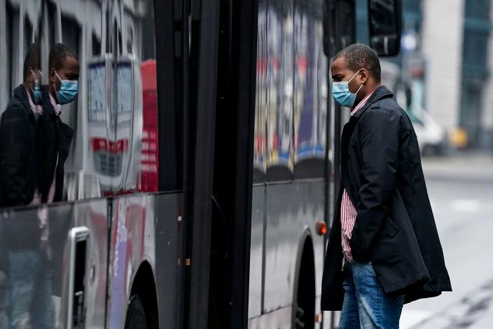 A commuter wearing a protective face mask catches a bus at the Gare Bruxelles-Central train station on May 4, 2020 in Brussels, amid the spread of the COVID-19 pandemic caused by the novel coronavirus. (Photo by Kenzo TRIBOUILLARD / AFP) (Photo by KENZO TRIBOUILLARD/AFP via Getty Images)