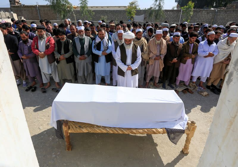 Afghan men pray in front of the coffin of one of three female media workers who were shot and killed by unknown gunmen, in Jalalabad