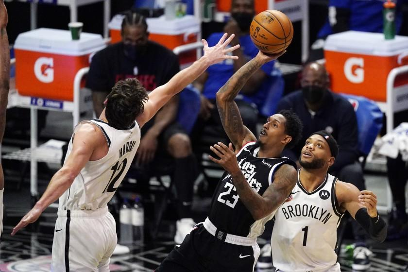 Los Angeles Clippers guard Lou Williams, center, shoots as Brooklyn Nets forward Joe Harris, left, and guard Bruce Brown defend during the first half of an NBA basketball game Sunday, Feb. 21, 2021, in Los Angeles. (AP Photo/Mark J. Terrill)