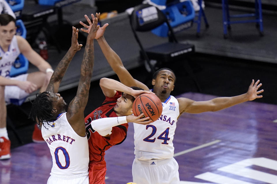 Eastern Washington guard Michael Meadows, center, gets pressure from Kansas guard Marcus Garrett (0) and teammate Bryce Thompson (24) during the first half of a first-round game in the NCAA college basketball tournament at Farmers Coliseum in Indianapolis, Saturday, March 20, 2021. (AP Photo/AJ Mast)