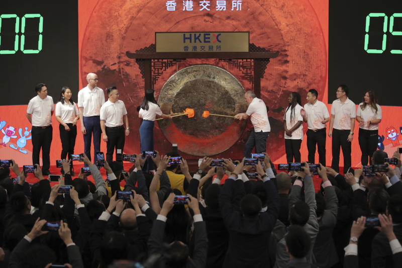 Members of Alibaba Group's digital economy customers and partners hit the gong during the Alibaba Group's listing ceremony at the Hong Kong Stock Exchange (HKEX) in Hong Kong, Tuesday, Nov. 26, 2019. (AP Photo/Kin Cheung)