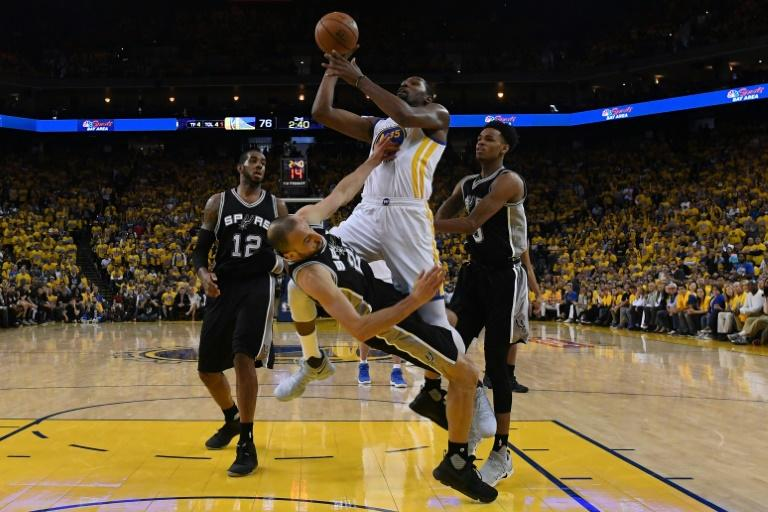 Manu Ginobili of the San Antonio Spurs draws a charge from Kevin Durant of the Golden State Warriors on May 14, 2017