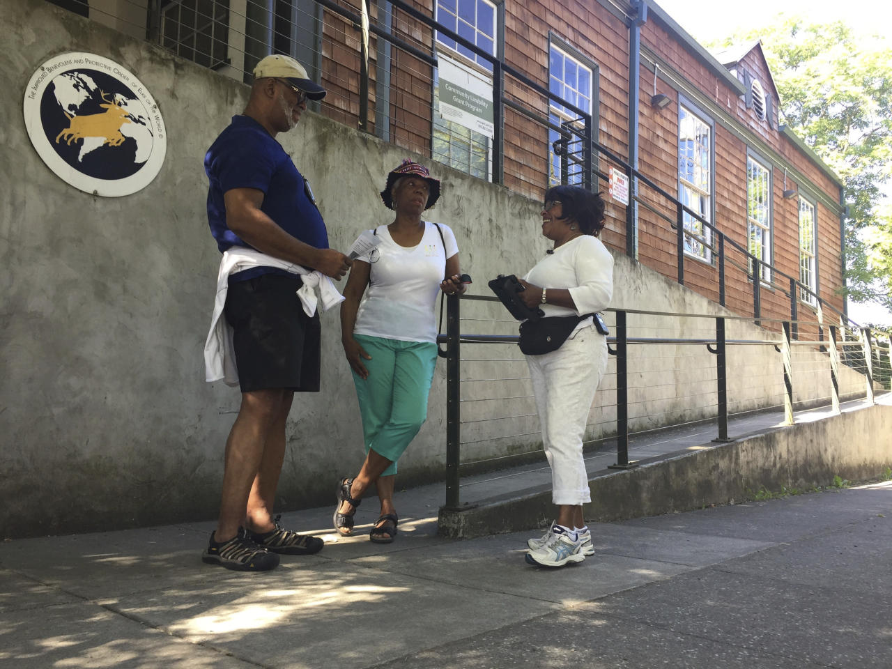 In this photo taken July 6, 2017, from left, Ron Young, Gahlena Easterly and Sharon Steen reminisce as they take a mile-long walk through North Portland, Ore. streets that once were full of black-owned homes and businesses. Researchers are studying whether jogging memories where they were made can help African-American seniors stay sharp and slow early memory loss. (AP Photos/Gillian Flaccus)