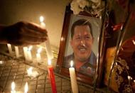 Supporters of Venezuelan President Hugo Chavez light candles while gathering in front of the Venezuelan embassy in Santiago, Chile, on March 5, 2013