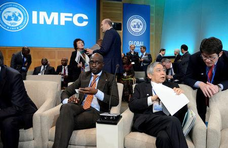 Bank of Japan Governor Haruhiko Kuroda chats with an aide as South Africa's Finance Minister Malusi Gigaba waits for the start of the International Monetary and Financial Committee (IMFC) Meeting, as part of the IMF and World Bank's 2017 Annual Spring Meetings, in Washington, U.S., April 22, 2017.   REUTERS/Mike Theiler