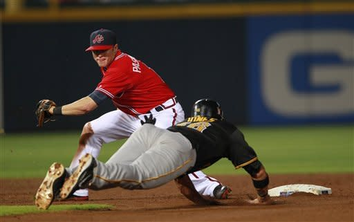 Pittsburgh Pirates' Rod Barajas (26) takes second base on a wild pitch as Atlanta Braves shortstop Tyler Pastornicky , top, waits on the late throw in the fourth inning of a baseball game Friday, April 27, 2012, in Atlanta. (AP Photo/John Bazemore)