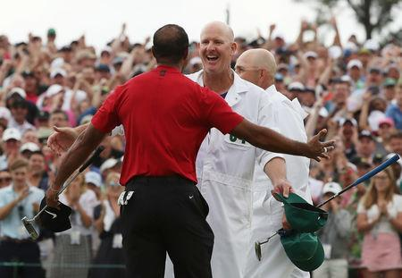Golf - Masters - Augusta National Golf Club - Augusta, Georgia, U.S. - April 14, 2019. Tiger Woods of the U.S. celebrates with caddie Joe LaCava on the 18th hole to win the 2019 Masters. REUTERS/Jonathan Ernst