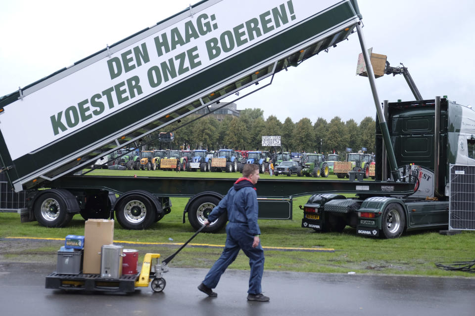 """A worker walks past a truck with a banner saying: """"The Hague: Cherish our farmers!"""", refrying to the government, as tractors driven by protesting farmers line up in the background during a protest in The Hague, Netherlands, Tuesday, Oct. 1, 2019. Thousands of Dutch farmers headed to the city on Tuesday, many driving in slow-moving convoys of tractors that snarled traffic in the morning rush hour, for a national day of protest to demand more respect for their profession. (AP Photo/Mike Corder)"""