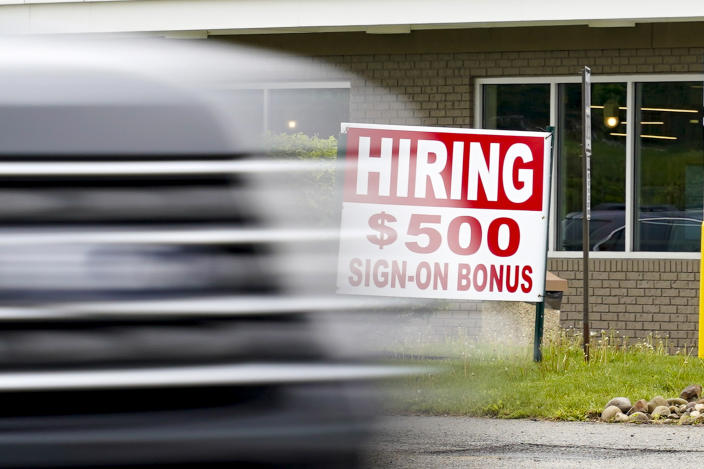 FILE—In this file photo from May 5, 2021, a vehicle speeds by a hiring sign offering a $500 bonus outside a McDonalds restaurant, in Cranberry Township, Butler County, Pa. Pennsylvania will resume work search requirements in July for hundreds of thousands of people receiving unemployment compensation, a top Wolf administration official said Monday, May 24, 2021. (AP Photo/Keith Srakocic, File)