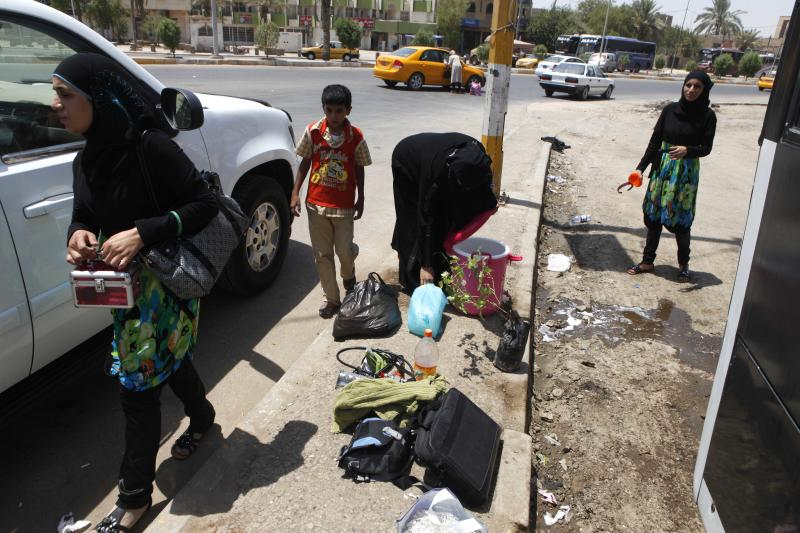 Iraqi refugees who have just returned from Syria unload their luggage from a bus in the Mansour neighborhood of Baghdad, Iraq, Friday, July 20, 2012. Iraq has flown hundreds of its citizens out of Damascus to escape the civil war in Syria, an official said Friday, while thousands of Iraqis poured through a major border crossing despite rebel takeovers of Syrian government posts and escalating violence near the two nations' boundaries. (AP Photo/Karim Kadim)