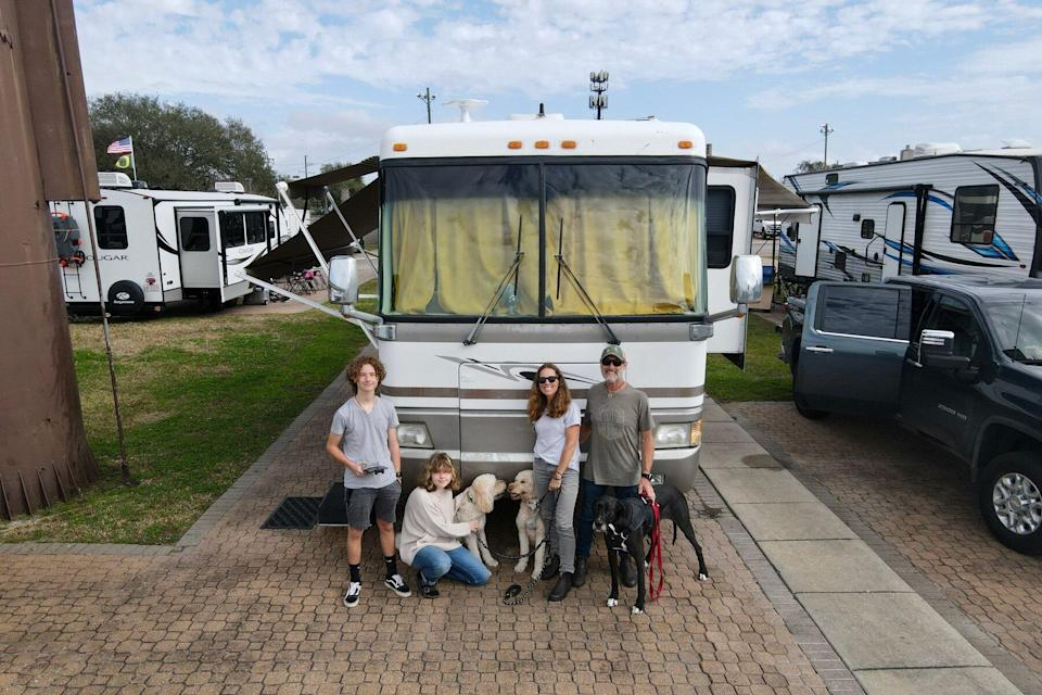 Photo of the Gamble Family in front of their RV Trailer with the three dogs